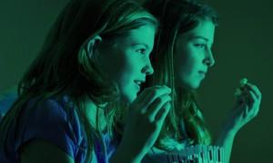 Two girls watching a film eating popcorn