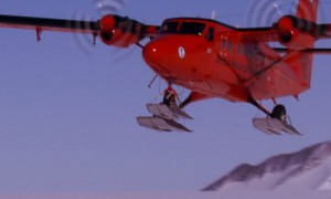 Twin Otter plane flying over ice sheet