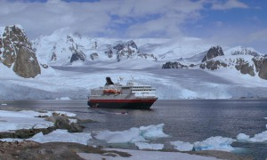 Antarctic panorama with tourist ship, penguin colony and tourists