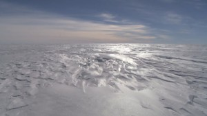 A slow pan across a flat, white polished ice wilderness in every direction showing how windy, hostile and bitterly cold Antarctica is.