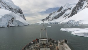 time lapse film of ship passing between ice covered mountains on both sides, whilst avoiding icebergs all in high speed